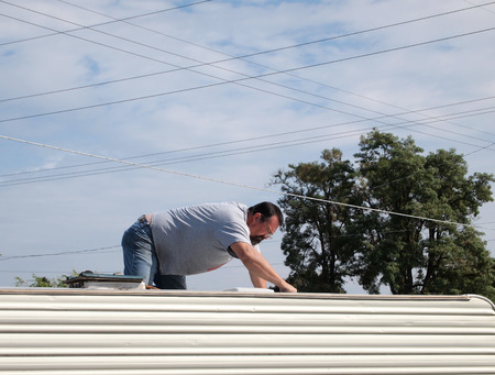 Young man on knees on top of travel trailer working