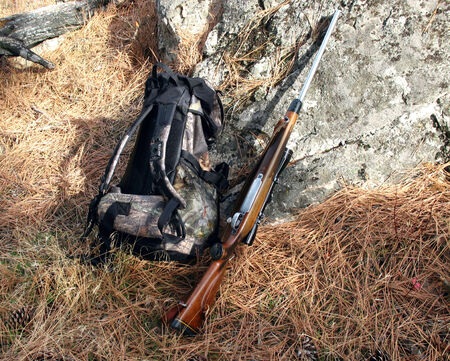 Hunting rifle and backpack leaning against rock