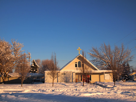 laden: Winter Church scene with clear blue sky photo.