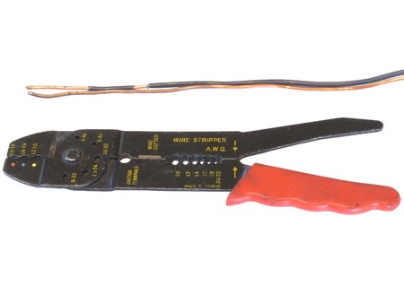 Copper wire and stripper pliers photo on white