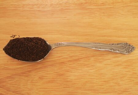 Horizontal photo of spoon of coffee grounds on wood grain table top