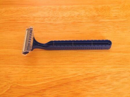 Horizontal photo of disposable shaving razor on wood grain table top.