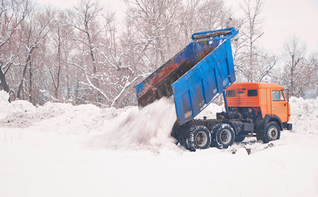 Cargo truck transporting snow pile. Wintern cleaning equipment