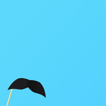Blue background with fake black mustache on a stick