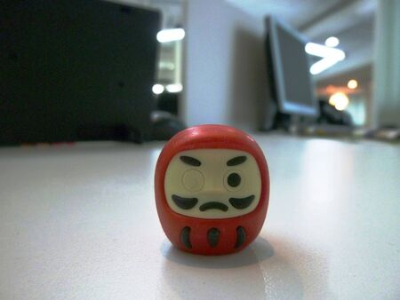 hope indoors luck: The prayerful rubber of Red Japanese doll Daruma on the desk Stock Photo