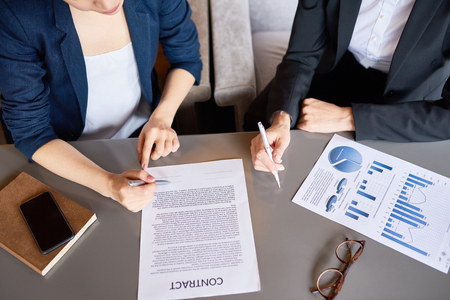 Top view of business table with contract document and unrecognizable people working at it making successful financial deal