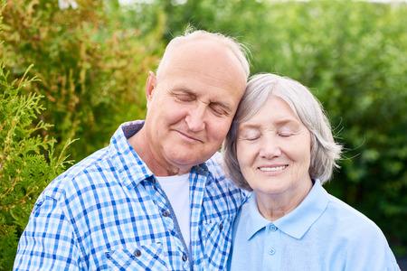 Portret van senior paar in liefde, omhelzen leunend op elkaar met de ogen gesloten en glimlachend staande in de prachtige groene tuin tegen bomen