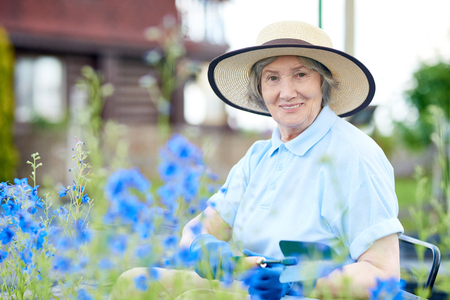Portrait of nice old woman wearing straw hat  posing in flower garden, smiling at camera while working