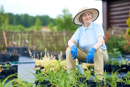 Portrait of smiling senior woman posing, looking at camera, while working in garden by the house