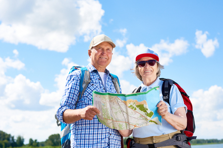 Portrait of active senior couple travelling on hiking trip, smiling looking at camera holding map together