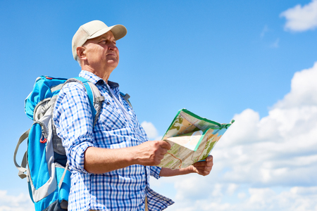Side view portrait of active senior man travelling on hiking trip wearing backpack, looking away holding map against clear blue sky