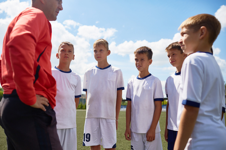 Portrait of young football players listening to coach explaining rules of game in field on sunny day Stock Photo