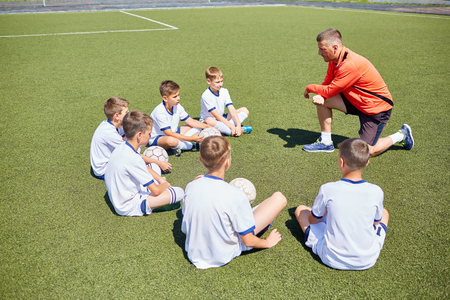 Junior football team sitting around coach listening to him in field on sunny day Stock Photo