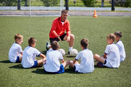前ゲームの講演を聞いてサッカーのフィールドでコーチの前に座っている男の子チームの肖像画