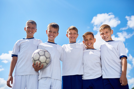 Portrait of junior football team posing smiling at camera with ball against clear blue sky in sunlight
