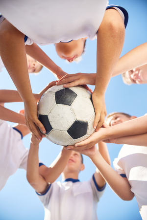 in low spirits: Low angle view of boys in junior football team holding ball together against clear blue sky