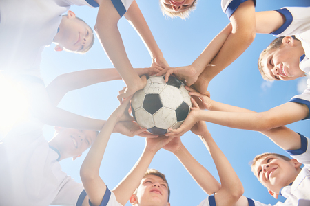 in low spirits: Low angle view of boys in junior football team standing in circle holding ball together against clear blue sky Stock Photo