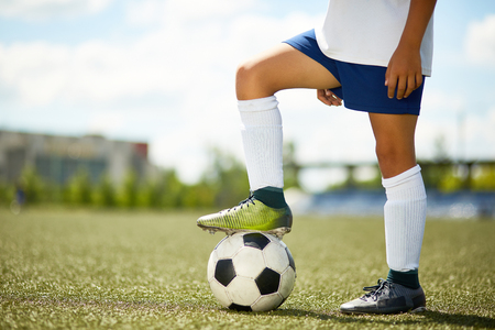 Side view portrait of unrecognizable young sportsman standing in football field with leg on ball Foto de archivo