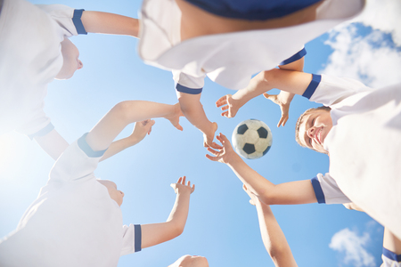 Low angle view of boys in junior football team jumping trying to catch ball against clear blue sky Stock Photo
