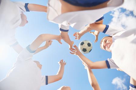 Vista de ángulo bajo de los niños en el equipo de fútbol juvenil saltando tratando de atrapar la bola contra el cielo azul claro Foto de archivo - 83464966