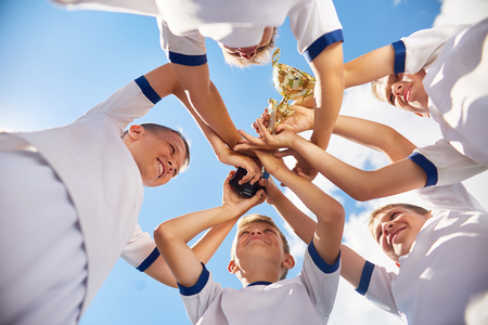 Low angle view of happy  boys in junior football team holding trophy cup together against clear blue sky and cheering