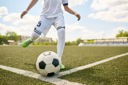 Closeup portrait of unrecognizable teenage boy kicking ball during football practice in field , focus on football  ball lying on grass Stock Photo