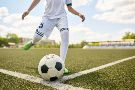 Closeup portrait of unrecognizable teenage boy kicking ball during football practice in field , focus on football  ball lying on grass 版權商用圖片