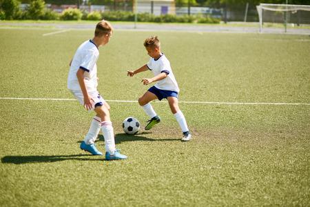 Portret van twee jongens die voetbal spelen tijdens ondergeschikte teampraktijk op gebied