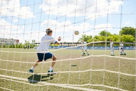 Vista traseira, retrato, de, adolescente, goleiro, pegando bola, durante, partida, entre, junior, futebol americano, equipes, tiro, atrás de, portão, rede Foto de archivo - 83465016