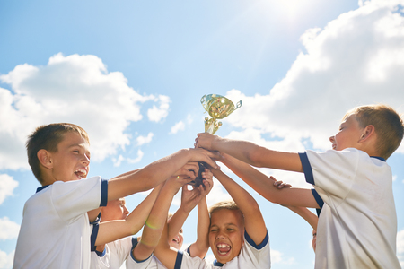 Team of children celebrating victory in sports, cheering and holding golden cup against clear blue sky