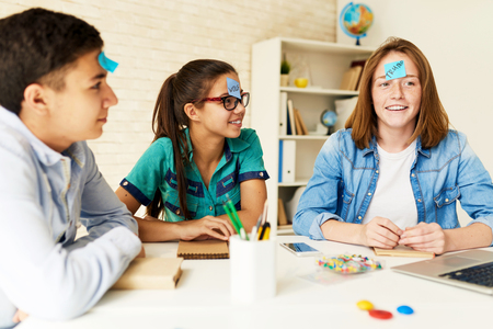 Group of children playing guessing game at table in classroom with names on their heads Imagens
