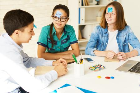 Grupo de adolescentes jugando juego de adivinanzas en la mesa en el aula con nombres en notas adhesivas Foto de archivo - 83465089