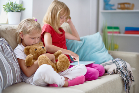 かわいい妹を自宅で静かな夜を楽しむ: 居心地の良いソファの上に座って、デジタル タブレット、背景にリビング ルームの素敵なインテリアに教育 写真素材