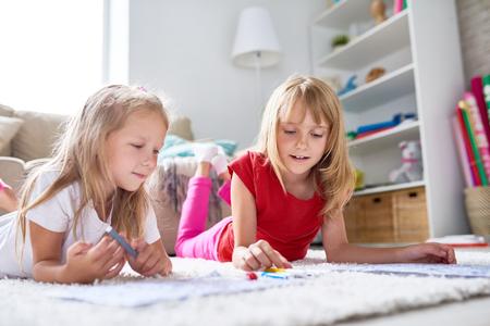 Creatieve kleine meisjes liggend op tapijt en afbeeldingen tekenen met viltstiften, mooi interieur van de woonkamer op de achtergrond Stockfoto