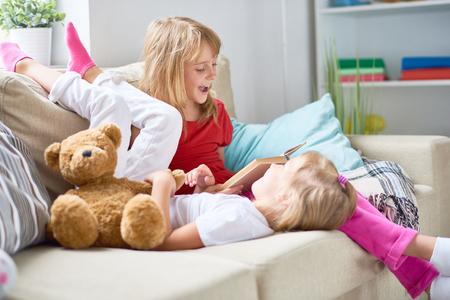 Mooie blondharige meisje lezen avontuur verhaal hardop, terwijl haar kleine zusje liggend op de bank en luisteren naar haar met belangstelling, interieur van gezellige woonkamer op de achtergrond