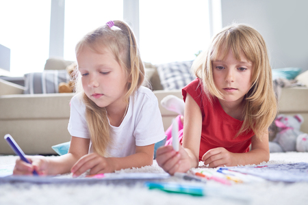 Portrait of pretty little girl choosing necessary felt-tip pen in order to color picture, her best friend lying on carpet next to her, interior of spacious living room on background
