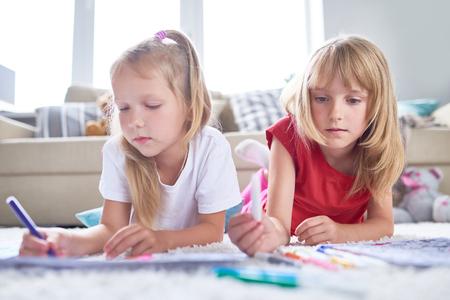Portret van mooi meisje die noodzakelijke viltpen kiezen om beeld te kleuren, haar beste vriend die op tapijt naast haar liggen, binnenland van ruime woonkamer op achtergrond