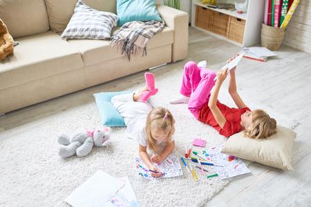 가정에서 보내는 자유 시간 : 아늑한 카펫에 누워있는 귀여운 소녀와 펠트 펜으로 그림 색칠하기, 여동생이 디지털 태블릿에서 게임하는 동안