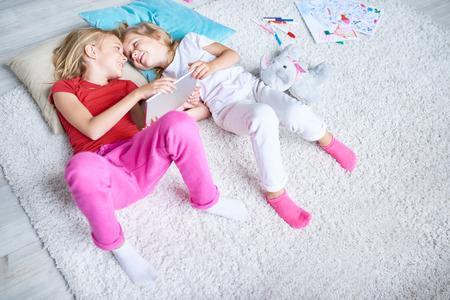 かわいい妹居心地の良いカーペットに横になっていると目と目を見て、彼らは手でモダンなデジタル タブレットを保持