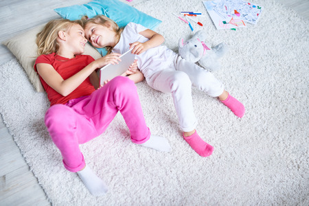Cute little sisters lying on cozy carpet and looking eye to eye, they holding modern digital tablet in hands