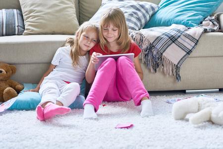 Jolie fille assise sur le sol et jouant au jeu d'ordinateur éducatif tandis que sa petite soeur mignonne reposant la tête sur son épaule et suivant ses actions avec intérêt. Banque d'images - 83829601
