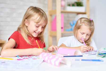 Mooie kleine deelnemers van het tekenen van klasse zit aan een bureau en kleurplaten met viltstiften, onscherpe achtergrond