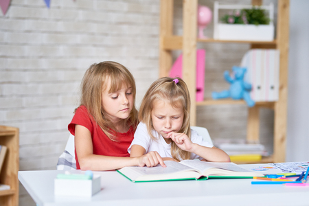 Adorable little sisters wrapped up in reading adventure story while sitting at table in their cozy bedroom Foto de archivo