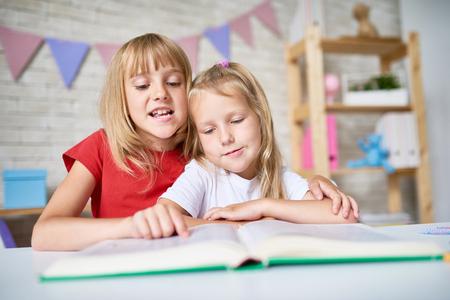 Retrato de niña bonita rubia abrazar suavemente a su hermanita mientras lee cuento de hadas en voz alta, interior de dormitorio encantador en el fondo Foto de archivo - 83829588