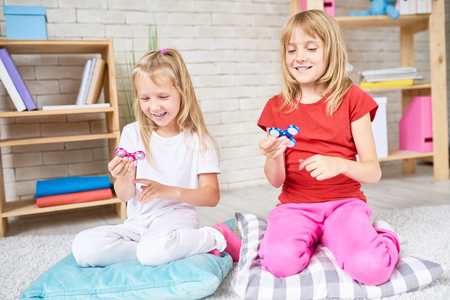 Cheerful blond-haired sisters gathered together in cozy living room and playing with popular fidget spinners