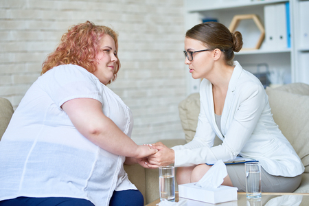 Portrait of beautiful female psychiatrist  offering psychological support to obese young woman holding hands and comforting her during therapy session on mental issues in doctors office. Stock Photo
