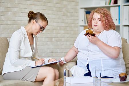 Portret van vrouwelijke psycholoog die nota's over klembord nemen terwijl het raadplegen van zwaarlijvige jonge vrouw die cupcakes over geestelijke wanorde en gezondheidskwesties eten