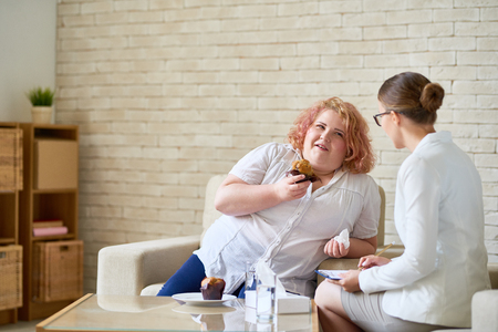 Portrait of young obese woman eating cupcakes and smiling during  therapy session with female psychiatrist