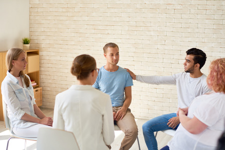 Group of young people sitting in circle during therapy session, one man comforting other participant patting him on shoulder with support and understanding