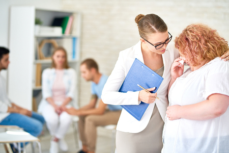 Portrait of young female psychiatrist, talking to obese woman crying in support group therapy meeting Stock Photo